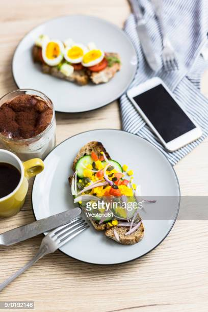 Vegetarian breakfast with bread, eggs and cucumber slices on plate, smartphone, latte macchiato, coffee cup