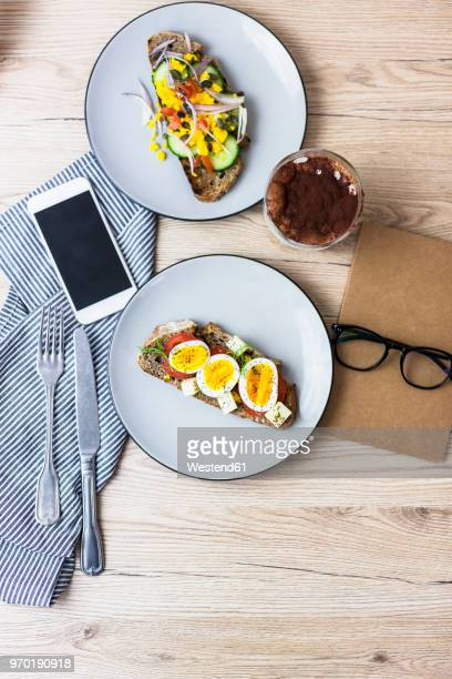 Vegetarian breakfast with bread, eggs and tomato slices on plate, latte macchiato, smartphone, notebook