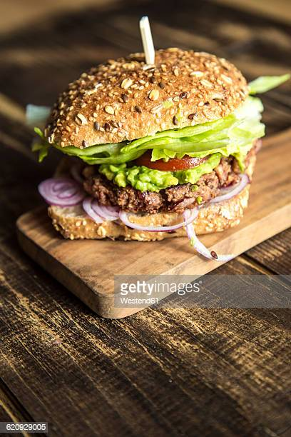 Vegetarian Burger with beetroot patty, avocado cream, salad and onions