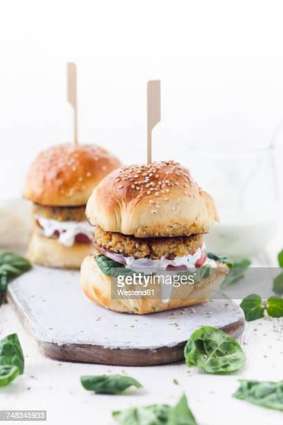 vegetarian burger with halloumi zucchini carrot patty, tzatziki sauce, homemade bun - veggie burgers stock pictures, royalty-free photos & images
