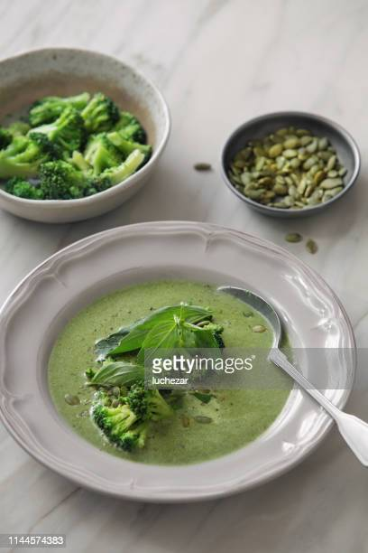 vegetarian creamy broccoli soup with pumpkin seeds and basil - pureed stock pictures, royalty-free photos & images