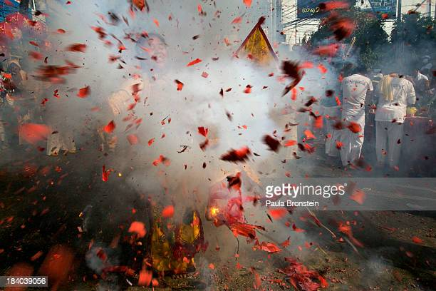 Vegetarian festival devotee dances as a firecracker explodes in front of her during the festival street procession in Phuket Thailand on October 11...