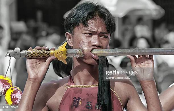 Vegetarian Festival Phuket town acts of self mutilation prayer in local shrines Phuket, Thailand here Man has sword piercing through his cheek