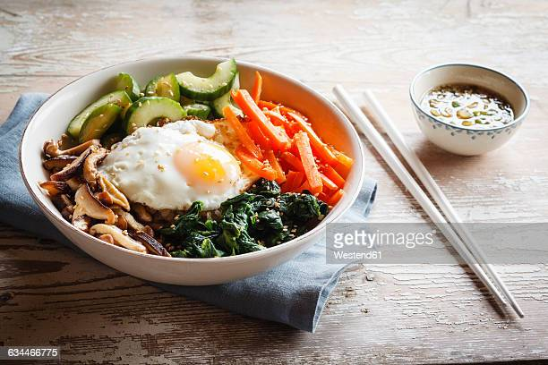 vegetarian korean rice bowl with mushroom, spinach, cucumber, carrot and fried egg - korean food stock pictures, royalty-free photos & images