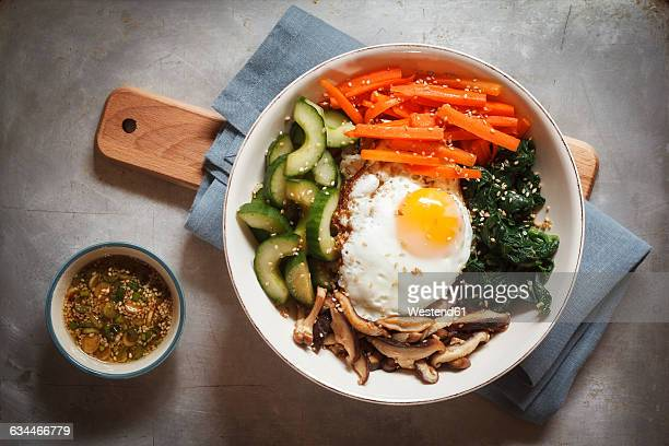 vegetarian korean rice bowl with mushroom, spinach, cucumber, carrot and fried egg - 韓国料理 ストックフォトと画像