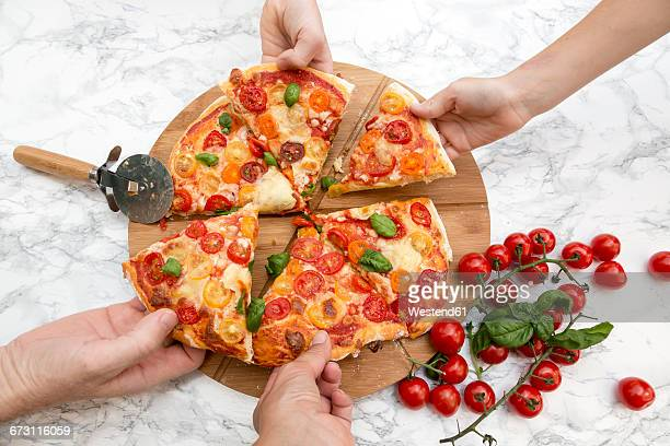 Vegetarian pizza with mozzarella and tomatoes, hands taking peace of pizza