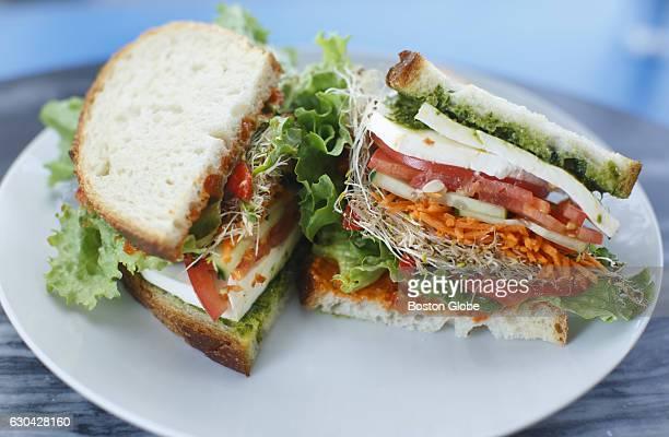 A vegetarian sandwich with fresh mozzarella sundried tomato aioli pesto sprouts lettuce tomato and cucumber all on sourdough pictured at Judith's...