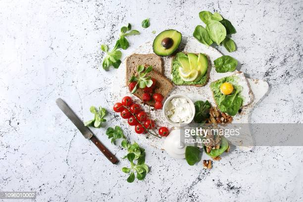 Vegetarian sandwiches with avocado, ricotta, egg yolk, spinach, cherry tomatoes on whole grain toast bread on white serving board with ingredients...