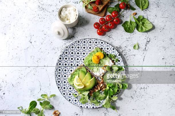 Vegetarian sandwiches with avocado, ricotta, egg yolk, spinach, cherry tomatoes on whole grain toast bread on ceramic plate with ingredients above...