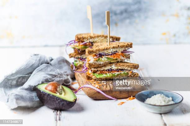 veggie sandwich, whole meal toast bread with grated carrot, red cabbage, white cabbage, avocado and cheese - sanduíche imagens e fotografias de stock