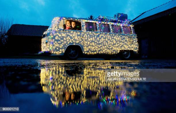 Vehicle appraiser and Doityourselfer Alexander Frank and his wife Katrin sit in their Volkswagen Microbus or 'Bulli' decorated with three chain of...