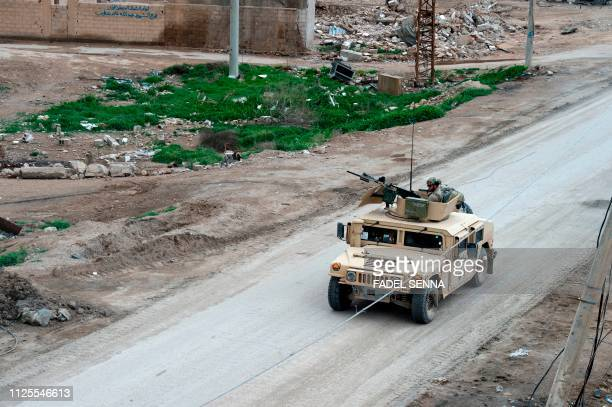 A vehicle belonging to the USled coalition drives down a street in the frontline Syrian village of Baghuz on February 17 2019