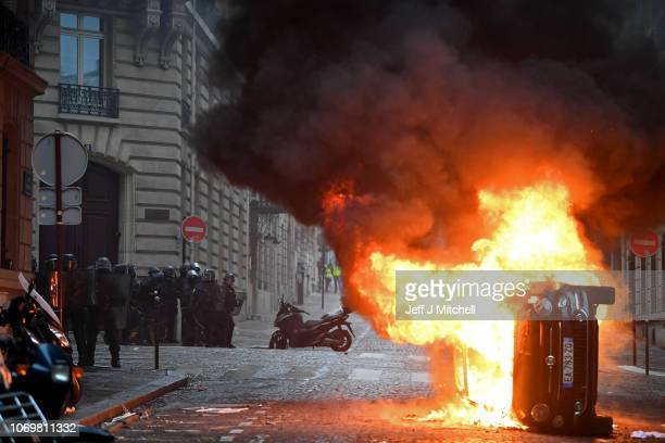 A vehicle burns from fires as protesters take part in the 'yellow vests' demonstration near the Arc de Triomphe on December 8 2018 in Paris France...