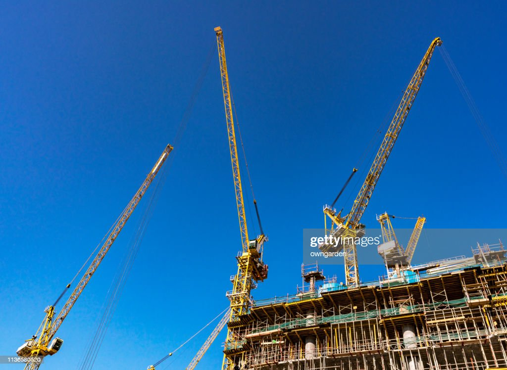 Vehicle By Cranes At Construction Site Against Sky : Stock Photo