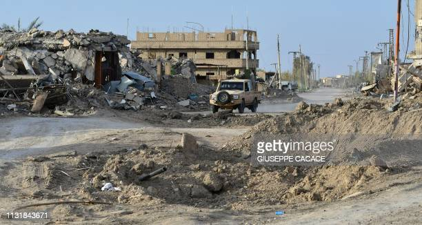 A vehicle carrying fighters of the USbacked Kurdishled Syrian Democratic Forces drives through the village of Sousa near the village of Baghouz in...
