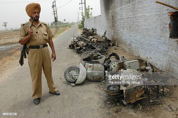 Vehicle damaged by activists and Indian Sikhs brandish swords as they raise slogans against the chief of the religious sect Dera Sacha Sauda ,...