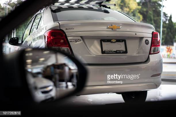 A customer uses a mobile device to take photographs of the interior of a vehicle at a General Motors Co Chevy dealership in Mexico City Mexico on...