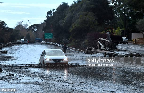 A vehicle drives across a flooded US 101 freeway near the San Ysidro exit in Montecito California on January 9 2018 Mudslides unleashed by a...
