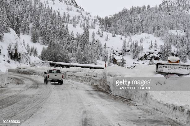 A vehicle drives along the road leading to the village of Val d'Isere in the French Alpes on January 9 2018 / AFP PHOTO / JEANPIERRE CLATOT