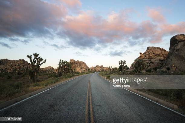 Vehicle drives at dusk in Joshua Tree National Park one day after the park reopened after being closed for two months due to the coronavirus pandemic...