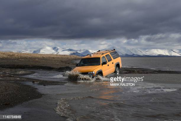 Vehicle drives beside the melting permafrost tundra on the edge of the Bering Sea at the town of Quinhagak on the Yukon Delta in Alaska on April 12,...