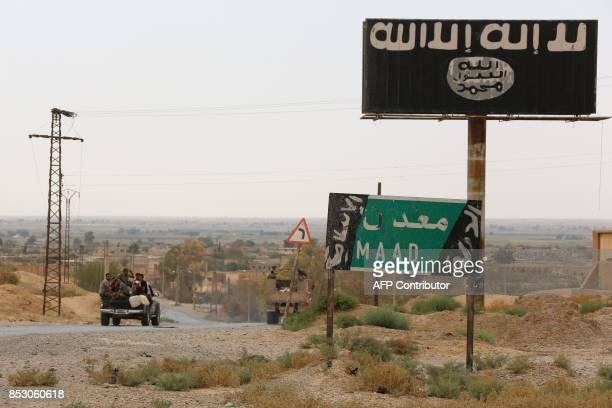 A vehicle drives past a billboard bearing the logo of the Islamic State group in Madan area in the countryside of Deir Ezzor on September 24 as...