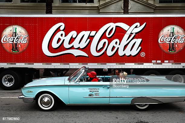 A vehicle drives past a CocaCola Co signage seen on a delivery truck in Miami Beach Florida US on Monday Oct 24 2016 The CocaCola Co is scheduled to...
