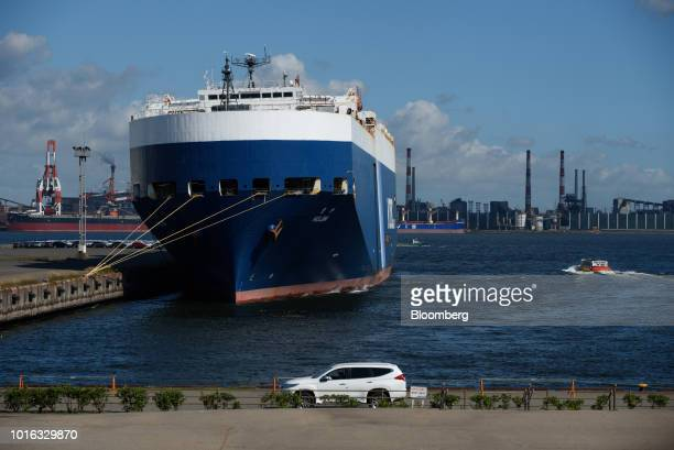 A vehicle drives past the Nippon Yusen KK Hojin vehicle carrier sitting berthed at the Nagoya Port in Nagoya Japan on Tuesday July 31 2018 Japan is...