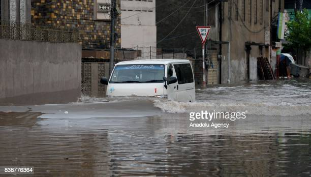 A vehicle drives through a flooded street after heavy monsoon rains hit the city of Rawalpindi Pakistan on August 25 2017 Heavy monsoon rains flooded...