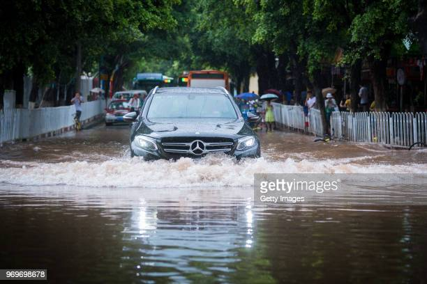 A vehicle drives through a flooded street on June 8 2018 in Guangdong China Typhoon Ewiniar the fourth typhoon of the year made landfall on Wednesday...