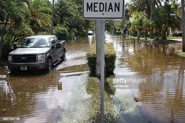 A vehicle drives through flooded streets caused by the combination of the lunar orbit which caused seasonal high tides and what many believe is the...