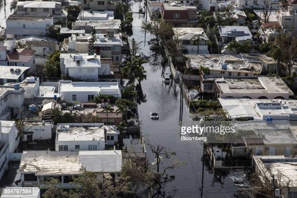 A vehicle drives through streets filled with floodwater near destroyed homes from Hurricane Maria in this aerial photograph taken above Barrio Obrero...