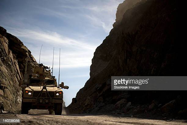 a mrap vehicle drives through the mountains of afghanistan. - mine resistant ambush protected stock pictures, royalty-free photos & images