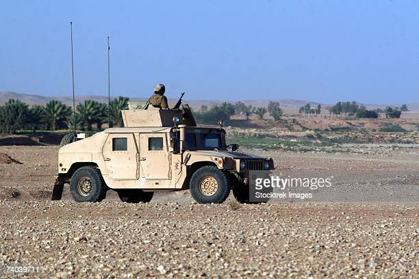 A vehicle filled with Marines conducting a mounted combat patrol near Al Asad, Iraq, June 15, sits at one of its checkpoints, observing the area briefly before moving on.