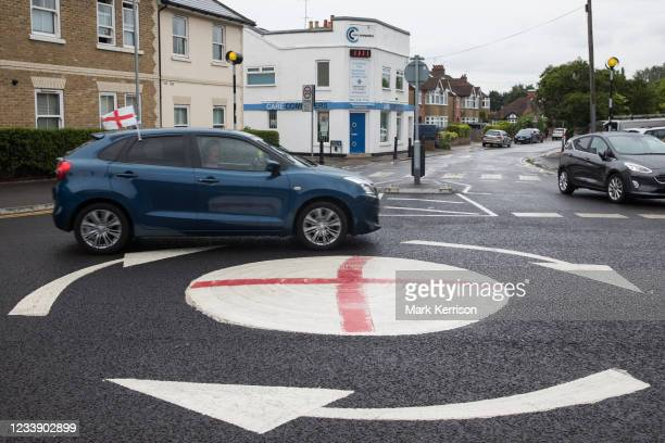 Vehicle flying a small England flag passes a mini-roundabout painted with the St George's flag on 10th July 2021 in Windsor, United Kingdom. The...