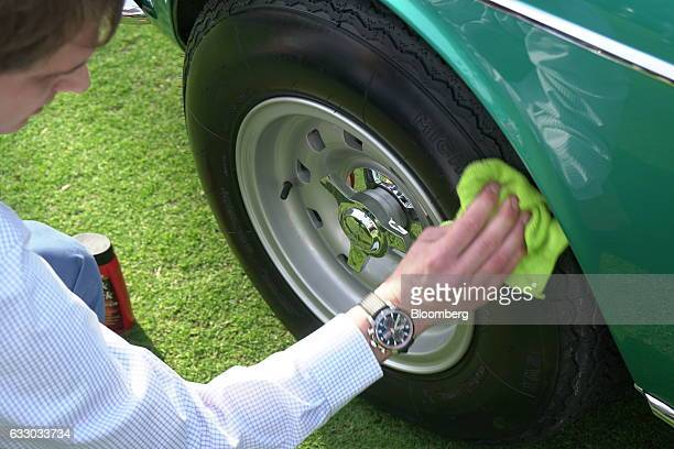 Vehicle handler polishes the tire of a a 1967 Ferrari SpA 330 GTC Speciale sports vehicle during the 26th Annual Cavallino Classic Event at the...