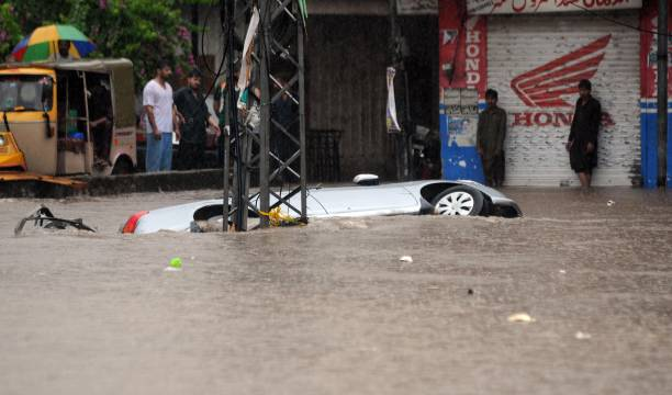 A vehicle is overturned in a flooded street after heavy monsoon rain hits the city of Rawalpindi Pakistan on August 07 2018 Pakistani army soldiers...