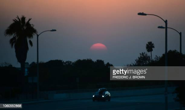 A vehicle is seen on a closed Pacific Coast Highway south of Malibu California as the sun sets over the Pacific Ocean on November 11 as firefighters...