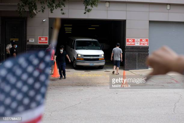 Vehicle leaves the Chinese consulate in Houston, Texas while protesters demonstrate outside on July 24 after the US State Department ordered China to...
