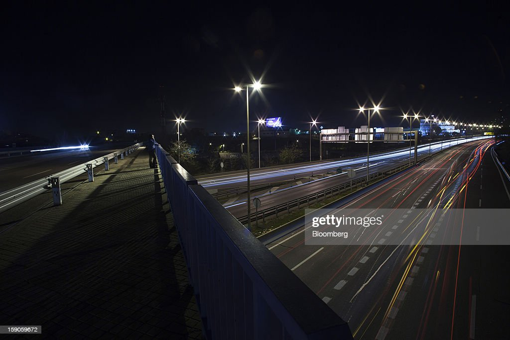 Vehicle light trails are seen at night on the M40 highway in Madrid, Spain, on Sunday, Jan. 6, 2013. In December, the Spanish parliament passed an energy law that imposed a 7 percent tax on electricity generation from Jan. 1 to plug the deficit. Photographer: Angel Navarrete/Bloomberg via Getty Images