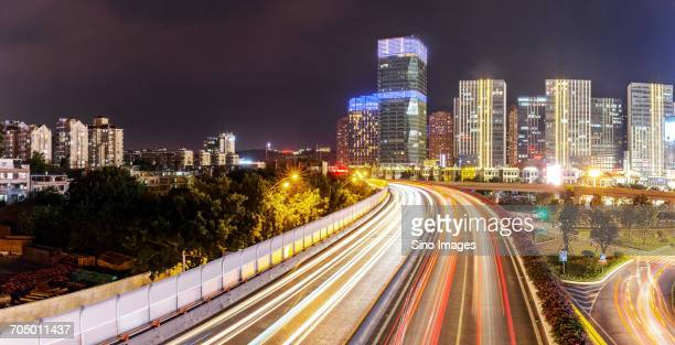 Vehicle light trails on elevated road in front of illuminated city buildings at night
