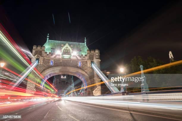 vehicle light trails on illuminated, tower bridge at night, london, england, uk - image stock pictures, royalty-free photos & images