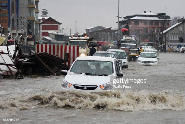 A vehicle makes its way through a waterlogged main street in Srinagar the summer capital of Indian administered Kashmir on April 062017 The valley...