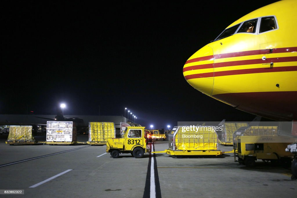 A vehicle moves package containers near a DHL Worldwide Express cargo jet at the company's hub of Cincinnati/Northern Kentucky International Airport in Hebron, Kentucky, U.S., on Wednesday, Aug. 16, 2017. The Deutsche Post AG, parent company to Worldwide Express, second-quarter operating profit jumped 12 percent as the German mail operator handled more express deliveries and won more business at its logistics unit. Photographer: Luke Sharrett/Bloomberg via Getty Images
