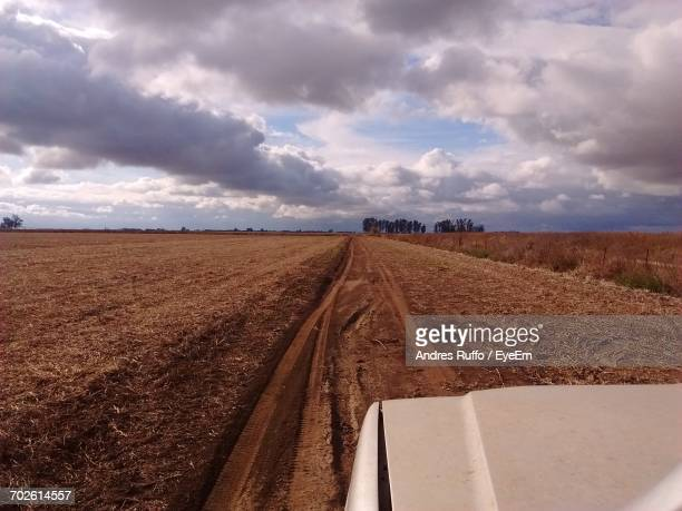 Vehicle Moving On Dirt Road Amidst Agricultural Field Against Cloudy Sky