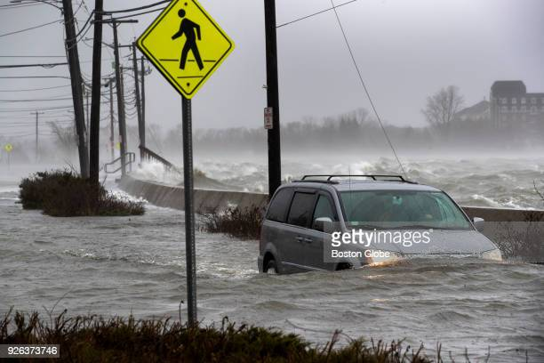 A vehicle navigates a flooded Squantum Street in the Squantum section of Quincy MA with Dorchester Bay in the background during a nor'easter storm on...