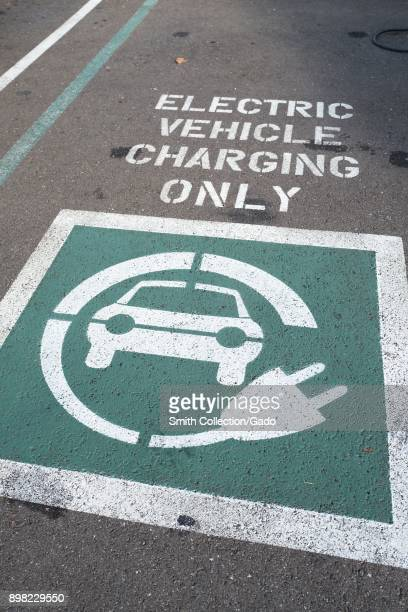Vehicle parking space with painted green and white markings indicating that the space is for electric vehicle charging only in a parking lot in the...
