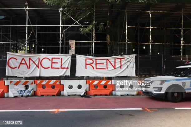 """Vehicle parks in front of a """"Cancel Rent"""" banner hung up by participants of a 'Resist Evictions' rally to protest evictions on August 10, 2020 in New..."""