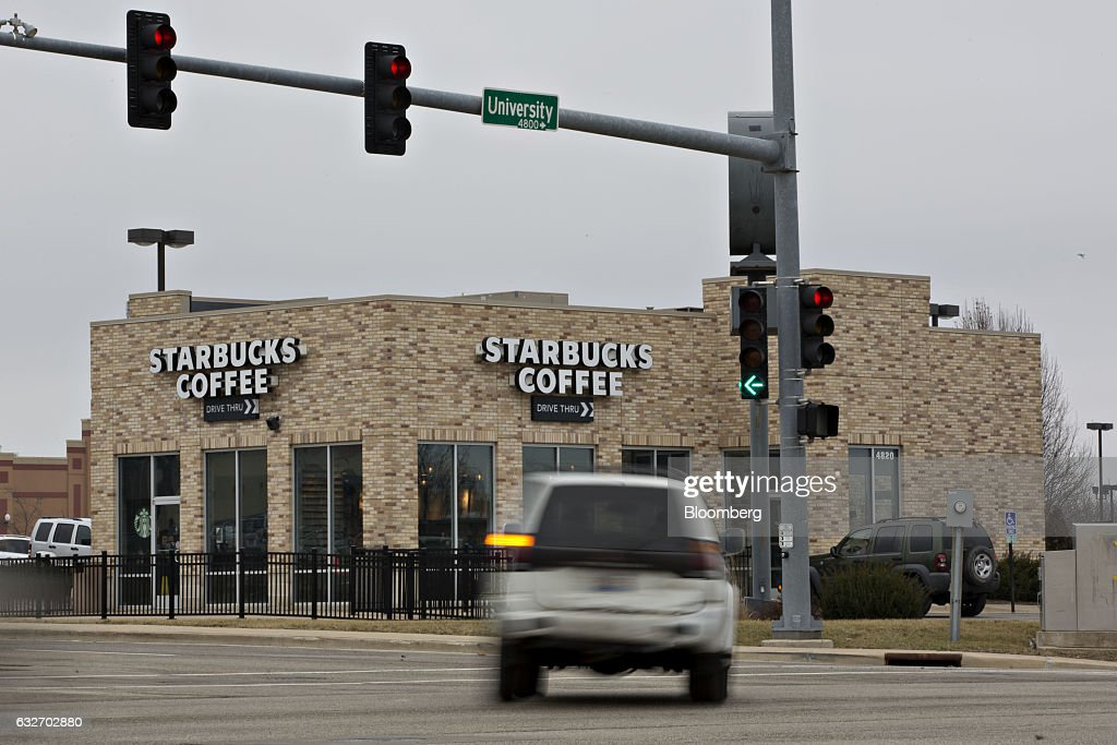 A vehicle passes in front of a Starbucks Corp. coffee shop in Peoria, Illinois, U.S., on Wednesday, Jan. 25, 2017. Starbucks Corp. is expected to release earnings figures on January 26. Photographer: Daniel Acker/Bloomberg via Getty Images