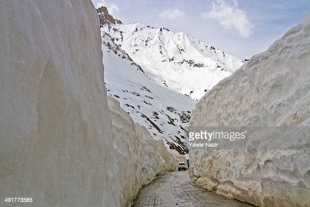 A vehicle passes through the snowcleared SrinagarLeh highway after it was reopened by authorities on May 17 2014 in Zojila 108 km east of Srinagar...